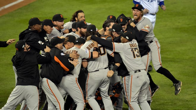 San Francisco Giants players celebrate on the field after defeating the Kansas City Royals during game seven of the 2014 World Series at Kauffman Stadium.