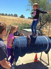 Lilly Green practices balancing on a vaulting horse, used to prepare children to ride horses.