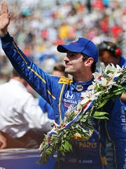 IndyCar driver Alexander Rossi celebrates winning the 100th running of the Indianapolis 500, Indianapolis Motor Speedway, Sunday, May 29, 2016.
