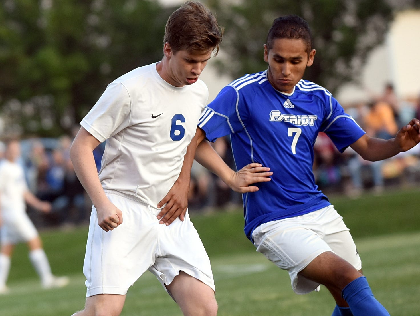 White House High junior forward Josh Dunlap maintains possession as Page junior Miguel Villanueva pressures during first-half action.