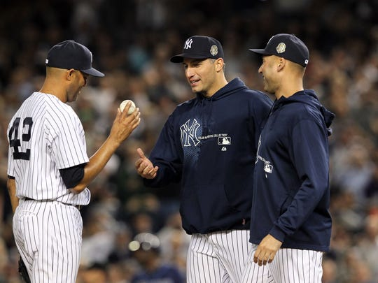 Yankees starting pitcher Andy Pettitte (46) and shortstop Derek Jeter (2) walk to the mound to remove relief pitcher Mariano Rivera.