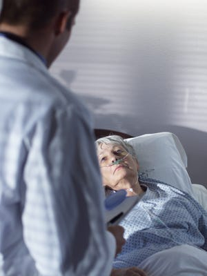 A male doctor comes in to visit and elderly woman as she lay in a hospital room.