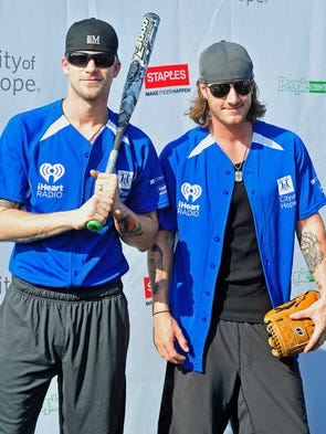 Tyler Hubbard, right, and Brian Kelley of Florida Georgia Line pose for a photograph during the City of Hope Celebrity Softball Game at Greer Stadium in Nashville, Tenn., Saturday, June 7, 2014.