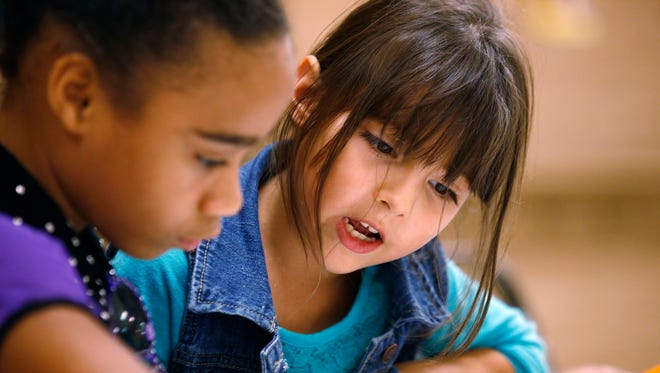 Chaantia Coleman, 10 (left), mentors Lesly Gonzalez, 7, during an after-school program at Wesley Community Center on Tuesday, Oct. 21, 2014, in Phoenix. Programs such as this one receive funding from Season for Sharing donations.