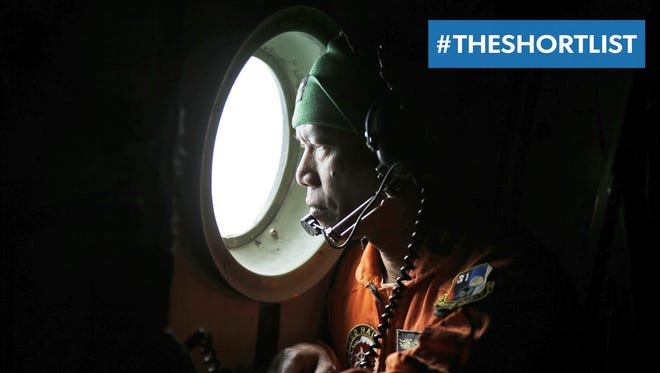 A crew member of an Indonesian Air Force C-130 airplane looks out of the window during a search operation for missing AirAsia flight 8501.