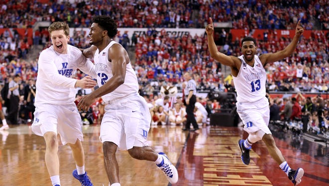 Justise Winslow #12 and Matt Jones #13 of the Duke Blue Devils celebrate with teammates after defeating the Wisconsin Badgers during the NCAA Men's Final Four National Championship at Lucas Oil Stadium on April 6, 2015 in Indianapolis, Indiana. Duke defeated Wisconsin 68-63.