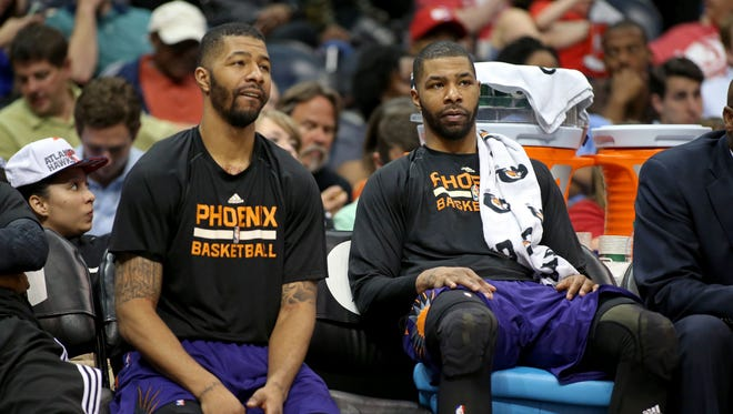 Suns forward Markieff Morris (left) and forward Marcus Morris (15) are shown on the bench in the fourth quarter of their game against the Atlanta Hawks at Philips Arena. The Hawks won 96-69.