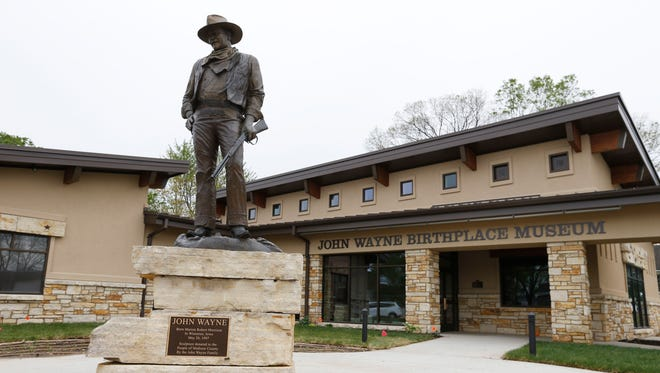 A sculpture of John Wayne, donated to the museum on what would have been Wayne's 100th birthday, is on display Wednesday, May 6, 2015, in front of the new John Wayne Birthplace Museum in Winterset, Iowa.