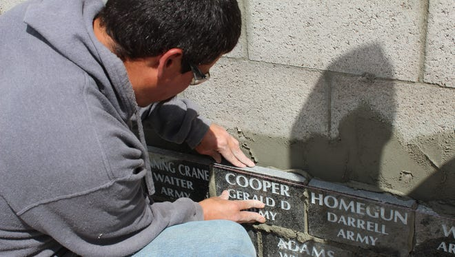A mason sets into place one of the 162 black marble tiles honoring Blackfeet veterans at the Montana Veterans Memorial in Great Falls
