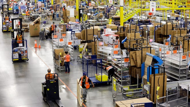 Workers fill orders at the Amazon fulfillment center on Cyber Monday, Dec. 1, 2014, in Lebanon, Tenn.