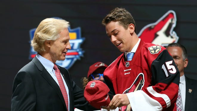 Dylan Strome puts on a hat after being selected third overall by the Arizona Coyotes in the first round of the 2015 NHL Draft at BB&T Center on June 26, 2015 in Sunrise, Florida.