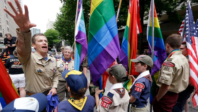 Scout leader Jesse Pacem, left, directs Cub Scouts and Boy Scouts as they prepare to lead marchers at the 41st annual Pride Parade on June 28, 2015, in Seattle.