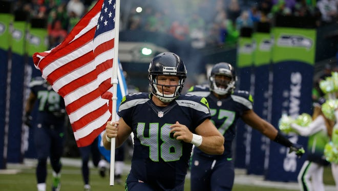Seattle Seahawks long snapper and military veteran Nate Boyer runs out of the tunnel with a U.S. flag at the start of a preseason NFL football game against the Denver Broncos, Friday, Aug. 14, 2015, in Seattle.