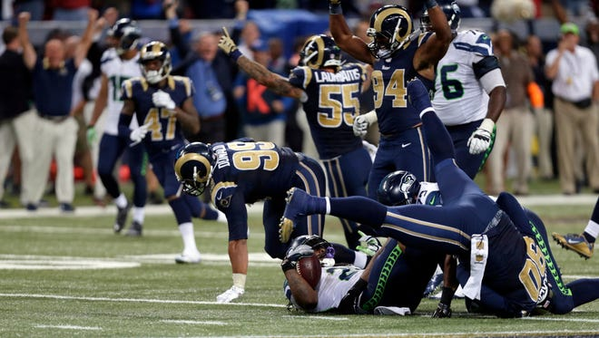 Seattle Seahawks running back Marshawn Lynch lands on his back as he is stopped on fourth down and St. Louis Rams players celebrate on the final play in overtime of Sunday's game in St. Louis. The Rams won 34-31. Lynch's mom was not pleased with the call.