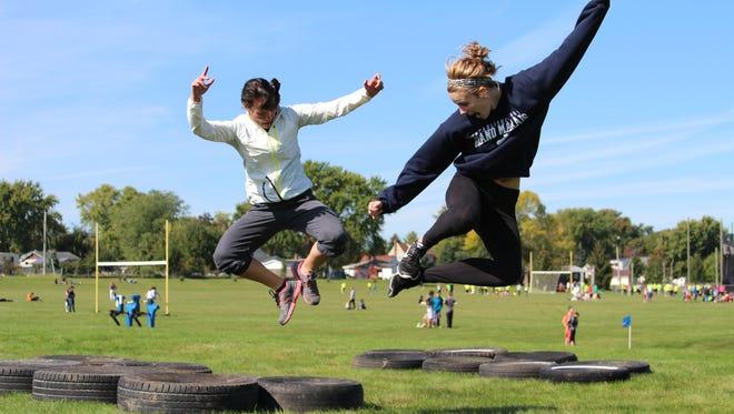 Sarah Dobbratz and Camryn Frye jump for health in-between runs during the Tough Warrior at Waupun Area Jr./Sr. High School.
