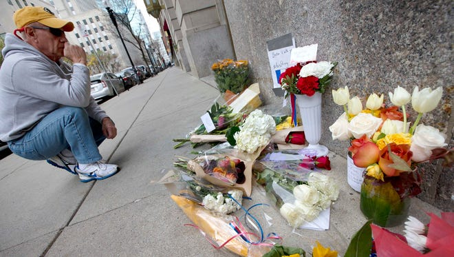 An unidentified man pauses after placing flowers on a make-shift memorial outside the French Consulate in Boston, Saturday, Nov. 14, 2015.