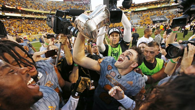 Arizona State senior quarterback Mike Bercovici holds up the Territorial Cup during post-game celebrations after ASU defeated Arizona 52-39 on Nov. 21, 2015 in Tempe, Ariz.