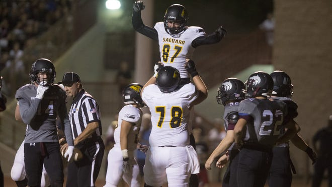 Saguaro's Michael Weinstein (78) lifts Jared Poplawski (87) in the air after a touchdown reception at Desert Mountain High School in Scottsdale, AZ  on October 9, 2015.