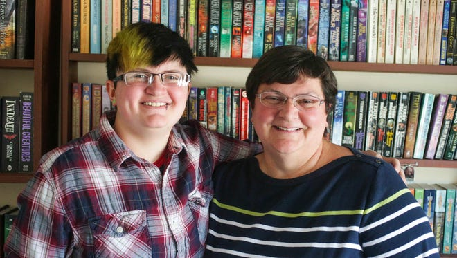 Transgender teen Alec Gorrell 18, left, and his mom Anita Gorrell, right, pose for a photo in front of their home library, Friday August 7th, 2015. Anita is president of Indy PFLAG, Parents, Families and Friends of Lesbians and Gays.