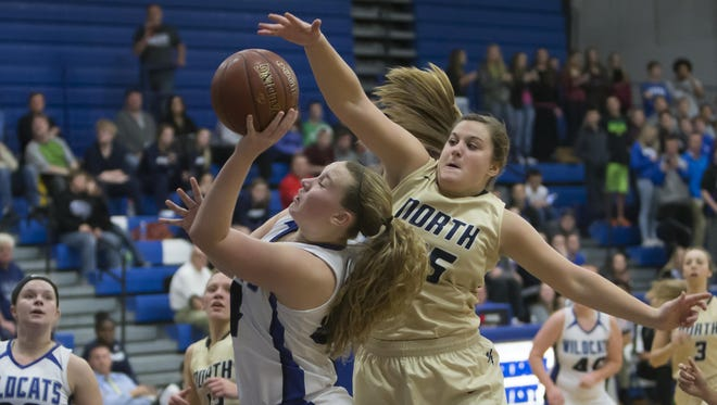 Emily Jacques of Oshkosh West attempts a shot as Appleton North's Grace Garvey (right) defends Friday in Oshkosh.