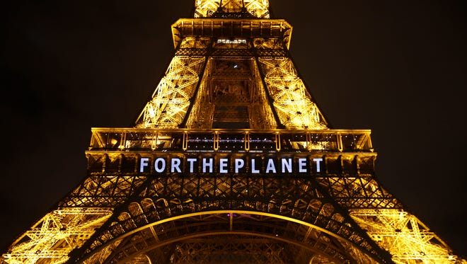 """The slogan """"FOR THE PLANET"""" is projected on the Eiffel Tower on Dec. 11."""