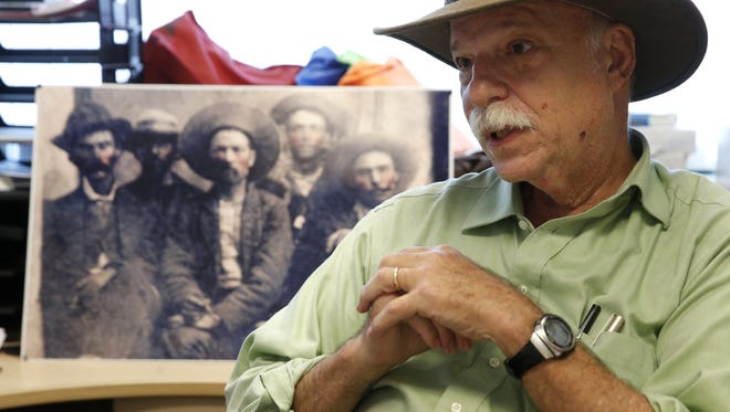 Dr. Michael Abrams speaks from his office at FAMU's campus Wednesday about a tintype photograph he believes is an original of outlaw Billy the Kid, the print can be seen on his desk in the background.
