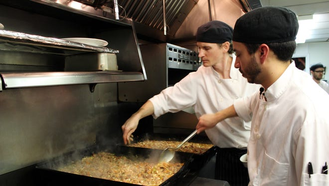 In this photo taken on Dec. 8, sous chefs Adan Franco, right, and Casey Davison of Sanford Restaurant season and stir cassoulet, which would be delivered to the Guest House homeless shelter in Milwaukee.