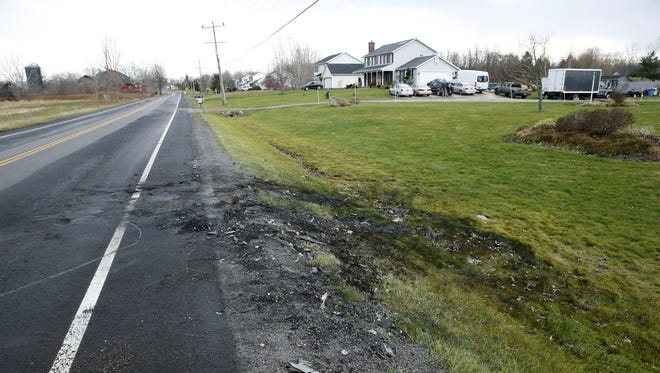 The grass appears scorched where a pastor and his daughter were rescued Christmas Eve from their vehicle after it was struck and caught on fire on Redman Road in Clarkson.