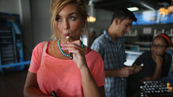 Chloe Lamb tries a flavor of e-liquid in her electronic cigarette as she shops for a flavor at the Vapor Shark store on September 6, 2013 in Miami, Fla.