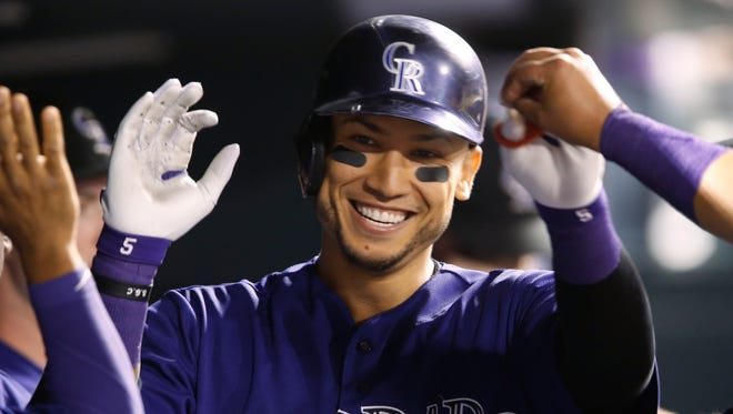 Colorado Rockies' Carlos Gonzalez smiles as he is congratulated after hitting a solo home run off Los Angeles Dodgers starting pitcher Mike Bolsinger in the fourth inning of a baseball game Friday, Sept. 25, 2015, in Denver.