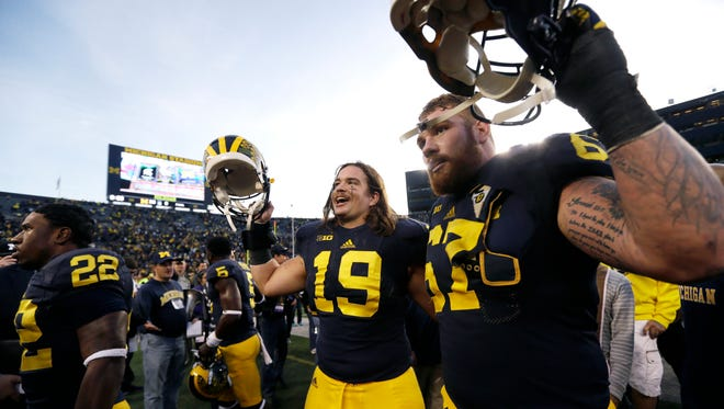 Michigan tight end Henry Poggi (19) and offensive lineman Kyle Kalis walk off the field after their 38-0 win over Northwestern on Saturday, Oct. 10, 2015, in Ann Arbor, Mich.