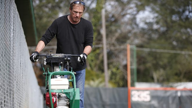 FAMU Head Coach Jamey Shouppe cuts sod from the area around the school's new alumni lounge on Wednesday to create a warning track for players. The sod is being transferred over to an area at Moore-Kittles Field where drainage issues had caused some flooding issues.
