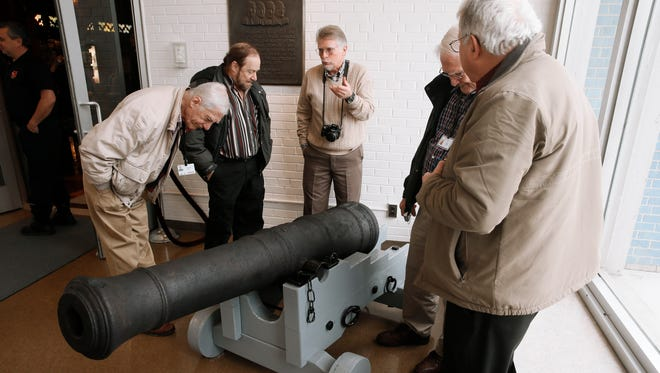 Visitors view a 18th Century British cannon that was found in the Detroit River in 2011 while on display, following a three-year restoration, at the Dossin Great Lakes Museum in Detroit on Dec. 10, 2014.
