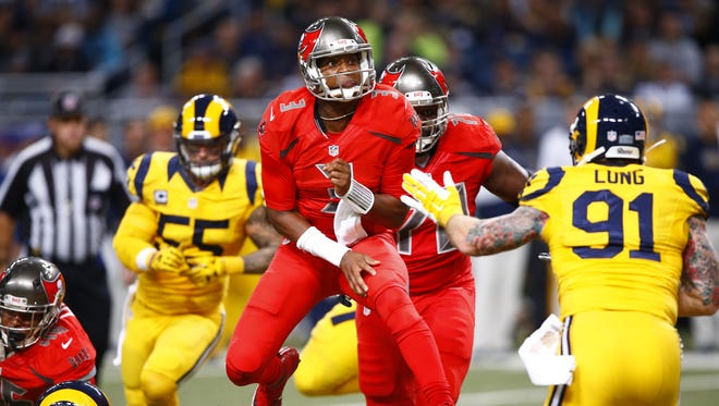 Tampa Bay Buccaneers quarterback Jameis Winston leaps after throwing a pass against the St. Louis Rams on Dec. 17, 2015, in St. Louis. Both teams were wearing Color Rush uniforms.