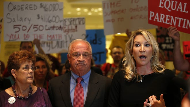 While Barbara DeVane, Robert Doyel and Heather Quick, ( left to right) explain their opposition to SB 668, they are photo bombed by the bill's supporters.