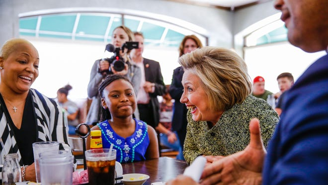 Democratic presidential candidate Hillary Clinton sits along side U.S. Rep. Andre Carson at the Lincoln Square Pancake House in Indianapolis.