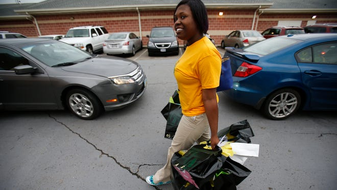 Taft High School English teacher Sinita Scott walks into the school with gifts for the 2016 graduating class, Thursday, May 12, 2016, at Taft High School in the West End. She started a Go Fund me page to raise money to buy gifts for each of the 87 graduating seniors.