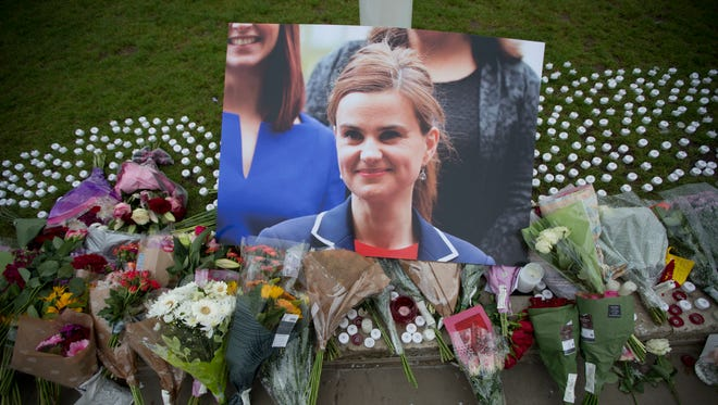 An image and floral tributes for Jo Cox, lay  on Parliament Square, outside the House of Parliament in London, Friday after the 41-year-old British Member of Parliament was fatally injured Thursday in northern England. The mother of two young children was shot to death Thursday afternoon in her constituency near Leeds. A 52-year-old man has been arrested but has not been charged. He has been named locally as Tommy Mair.