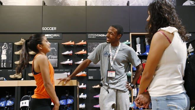 N'aithan Scott helps 12-year-old Savannah Valenzuela (left) pick out a new pair of track shoes at Dick's Sporting Goods in Glendale. Scott is a world-class 110-meter hurdler who's part of the Contenders program.