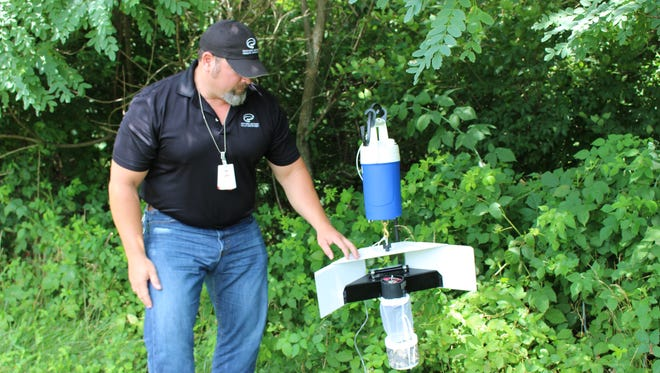 Jimmy Newman shows off the Northern Kentucky Health Department's mosquito traps. The traps use dry ice and lights to attract and capture the mosquitoes in a mesh bag.