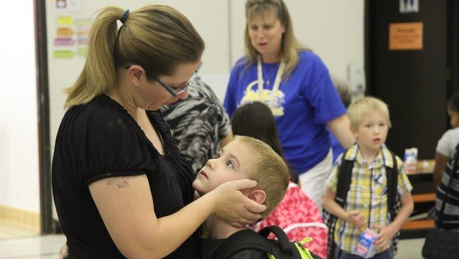 Callie Mayrhofen hugs her son, Kyle in the school cafeteria at Sunset Elementary. Thursday was the first day of school for all kids in kindergarten and grades 1, 6, 7, and 9.