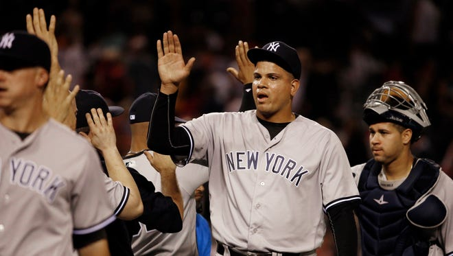 New York Yankees closer Dellin Betances, center, catcher Gary Sanchez, right, and teammates celebrate their 5-1 win over the Los Angeles Angels in a baseball game in Anaheim, Calif., Saturday, Aug. 20, 2016.