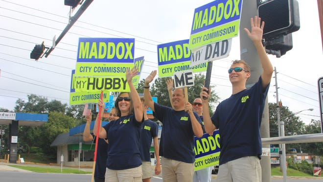Tallahassee City Commissioner Scott Maddox, his family and supporters wave to voters on Tuesday.. Maddox was re-elected in the primary, defeating three other candidates to avoid a run-off.