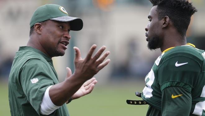 Packers safeties coach Darren Perry (left) speaks with rookie safety Kentrell Brice (29) during training camp.