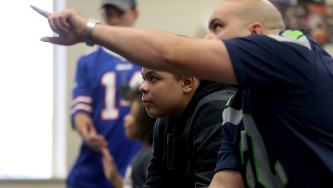 RPD officer, Mike Ciulla, and Davante Weiford play  Madden 17.  City Youth were invited to a video game tournament with the Rochester Police Department at A Gamers Nostalgia.