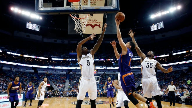 Suns guard Devin Booker (1) goes to the basket between Pelicans forward Terrence Jones (9) and guard E'Twaun Moore (55) in the first half in New Orleans, Friday, Nov. 4, 2016.