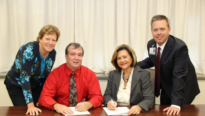 Dr. Walter Gianelle, MD, Your Doc's In President/CEO, seated left, and Dr. Peggy Naleppa, MS, MBA, FACHE, President/CEO of the Peninsula Regional Health System, seated right, sign a partnership agreement that will created a Your Doc's In urgent care center near Salisbury University owned and operated by the two healthcare leaders.  Joining them at the signing ceremony are Angela Gianelle, Chief Financial Officer, Your Doc's In, and Steve Leonard, Vice President of Operations Optimization and Innovation at Peninsula Regional Medical Center.