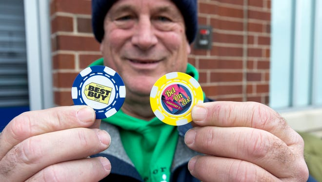 Mike Franke holds a pair of commemorative chips he got from Best Buy after arriving at the Delafield store a week in advance to be first in line on Thursday.