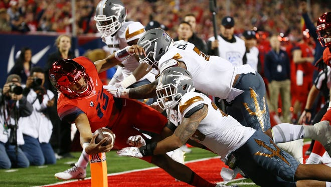 Arizona quarterback Brandon Dawkins dives and places the ball over the pylon for a touchdown against ASU in the first half during the 90th Territorial Cup game on Nov. 25, 2016 at Arizona Stadium in Tucson, Ariz.