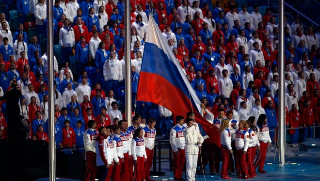 The Russian flag is raised during the closing ceremony for the Sochi 2014 Olympic Winter Games at Fisht Olympic Stadium.